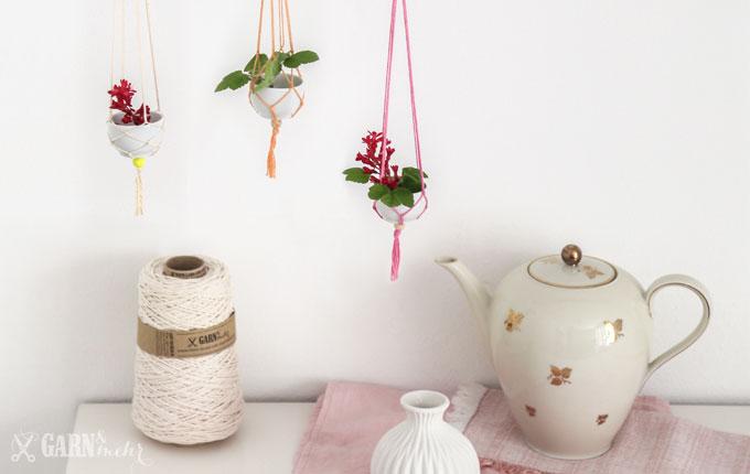 Stillleben mit Vintage Teekann und Garnkone mit 3 hängenden Mini-Vasenn aus Porzellanschalen mit rosa Garn und Makramee