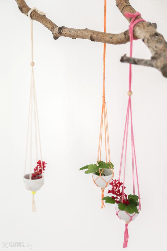 Ast mit 3 hängenden Mini-Vasen aus Porzellanschalen mit Garn in Frühlingsfarben, in Makramee-Technik hergestellt mit frischen Blüten